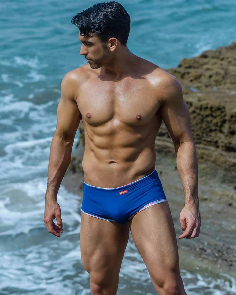 CHirs gogo dancer wears reversible blue swim trunks